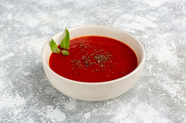 Heerlijke tomatensoep in witte plaat op grijs-wit, soep maaltijd diner plantaardig voedsel Gratis Foto
