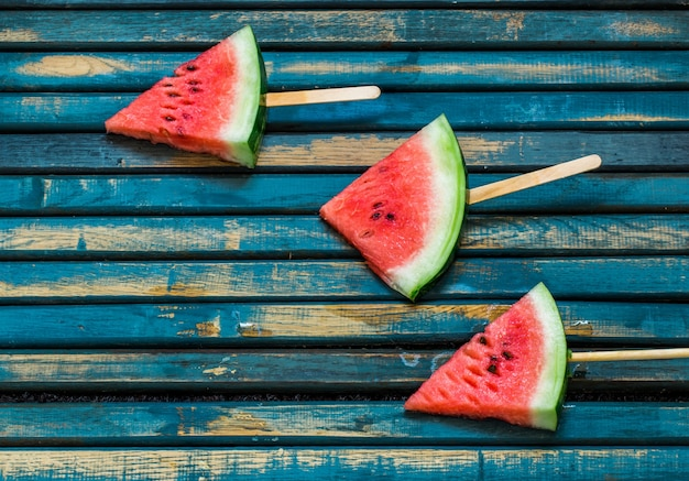 Heerlijke verse watermeloen. roomijs met watermeloen. heerlijke watermeloen op een blauwe houten achtergrond. detailopname. plaats voor tekst. Gratis Foto
