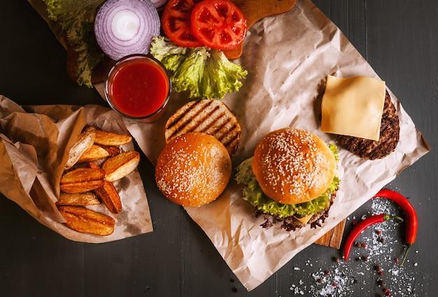 Heerlijke verse zelfgemaakte hamburger op een houten tafel. naast het component aan hamburger, houten bakjes, gebakken aardappelen en chili peper. een glas tomatensap Premium Foto