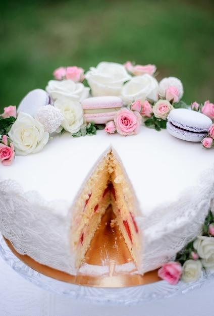 Heerlijke witte cake versierd met roze bitterkoekjes en rozen Gratis Foto