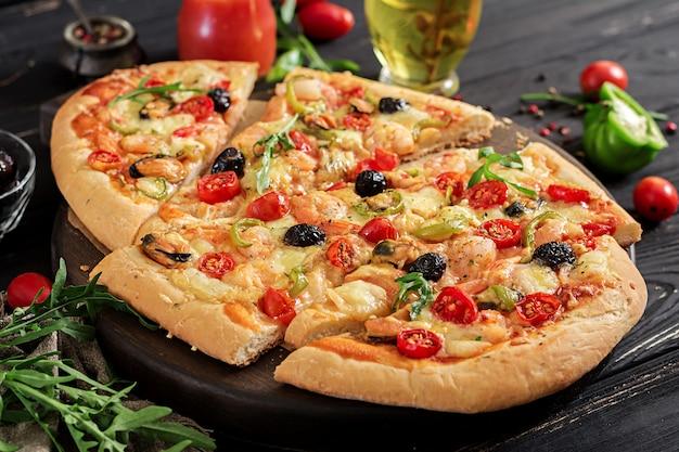 Heerlijke zeevruchtengarnalen en mosselenpizza op een zwarte houten lijst. italiaans eten. Gratis Foto