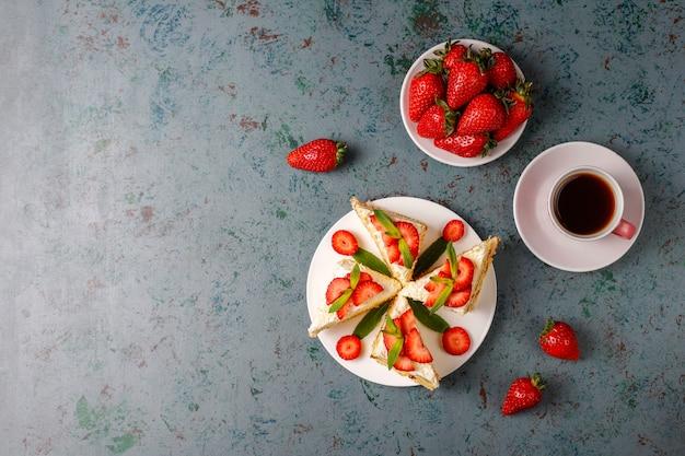 Heerlijke zelfgemaakte aardbeientaart segmenten met room en verse aardbeien, bovenaanzicht Gratis Foto