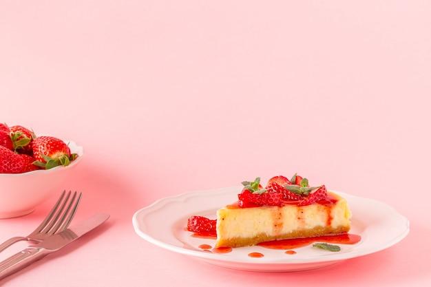 Heerlijke zelfgemaakte cheesecake met aardbeien op roze. Premium Foto