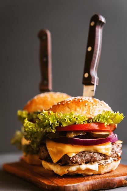 Heerlijke, zelfgemaakte hamburger om van te watertanden. op de houten tafel. de hamburgers zijn ingevoerde messen. Premium Foto