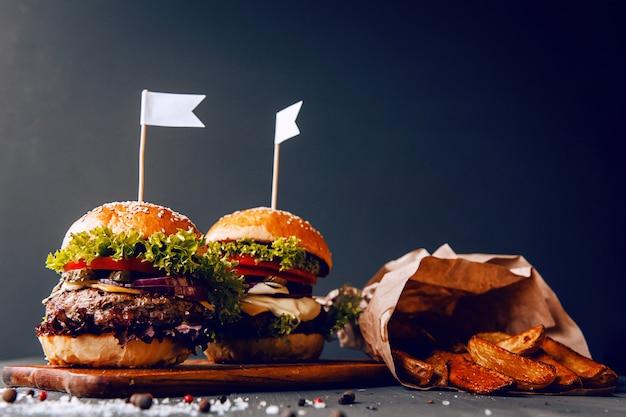 Heerlijke, zelfgemaakte hamburger om van te watertanden. op de houten tafel. Premium Foto