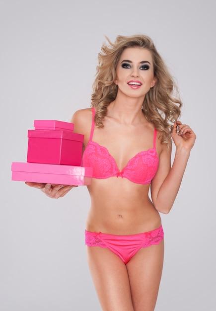 Heet meisje in roze lingerie met stapel geschenken Gratis Foto