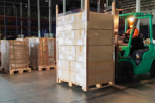 Heftruckchauffeur laden van zware zending pallet goederen in magazijn Premium Foto