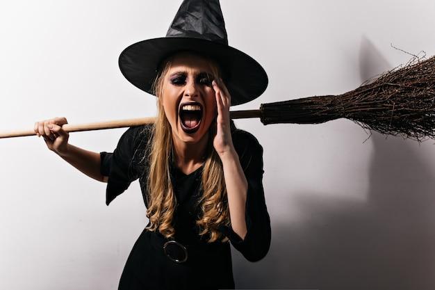 Heks met lang blond haar die op witte muur gillen. jonge vrouwelijke tovenaar die haar magische bezem houdt. Gratis Foto
