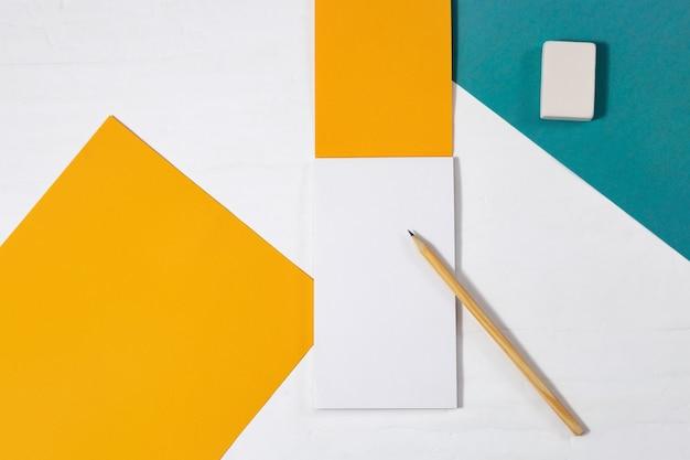 Helder geel tekenblok, houten potlood, gum op tafel. objecten voor tekenen op een lichte desktop. bovenaanzicht met kopie ruimte. plat leggen. Premium Foto