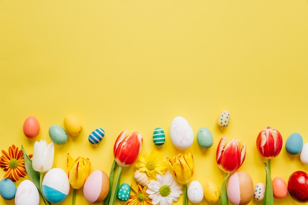 Helder gekleurde eieren met bloemen op geel Gratis Foto