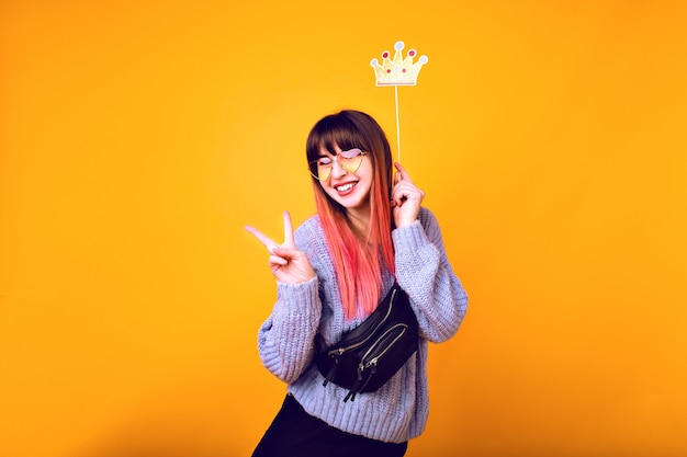 Helder grappig portret van vrolijke hipster vrouw met felroze haar, gezellige trui dragen, nep feestkroon vasthouden en glimlachen, klaar voor feest, gele muur. Gratis Foto
