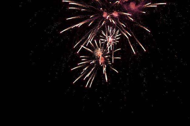 Helder kleurrijk vuurwerk en begroeting van verschillende kleuren in de nachtelijke hemel achtergrond. selectieve aandacht Premium Foto