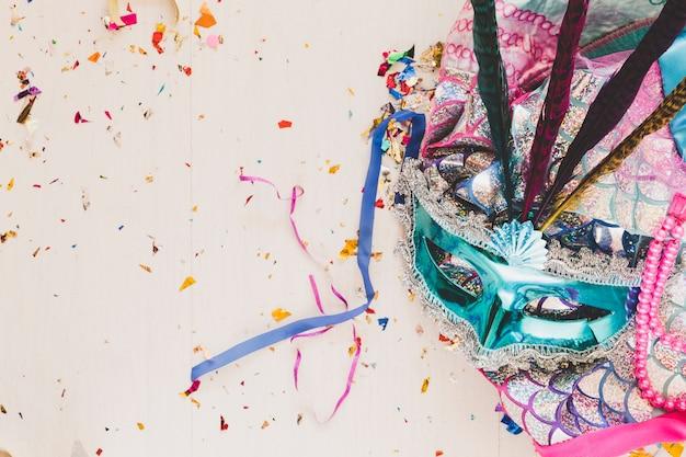 Helder kostuum met masker in confettien Gratis Foto