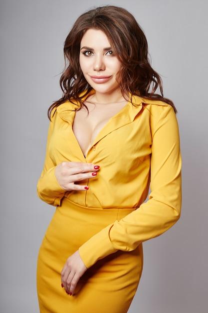 Helder lenteportret van een vrouw in een gele rok en een blouse. lang krullend haar en mooie dikke lippen. vrouw met een zomerse bui poseren Premium Foto