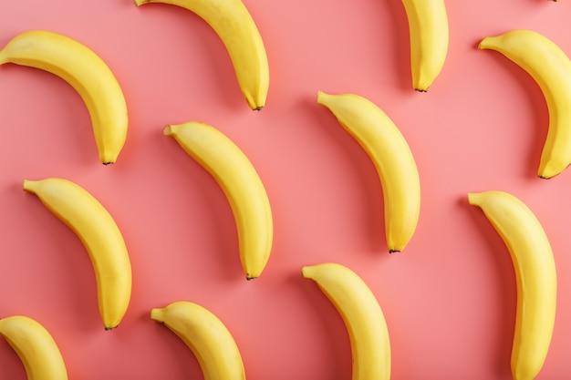 Helder patroon van gele bananen op een roze achtergrond. uitzicht van boven. plat leggen. fruit patronen Premium Foto