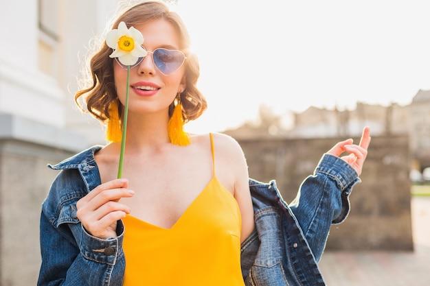 Helder portret van mooie vrouw met bloem, gele jurk, denim jasje, hipster stijl, zomer modetrend, glimlach, trendy zonnebril Gratis Foto
