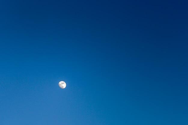 Helder verlichte maan in een wolkenloze donkerblauwe lucht, natuur, landschap Premium Foto