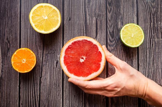 Heldere citrusvruchten op een houten donkere achtergrond. Premium Foto