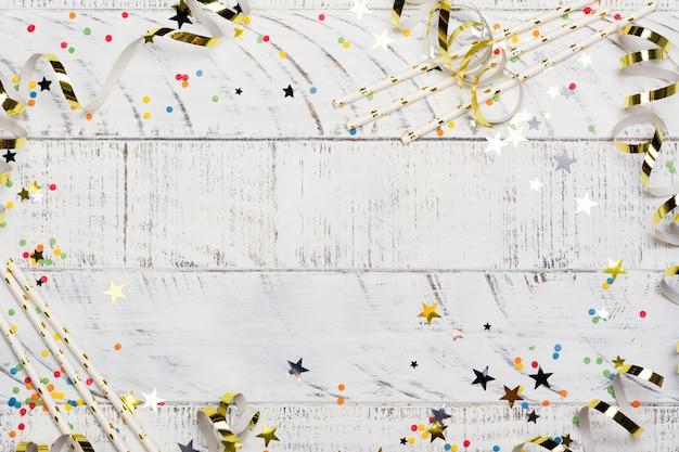 Heldere feestelijke carnaval achtergrond met hoeden, slingers, confetti en ballonnen op witte achtergrond Premium Foto