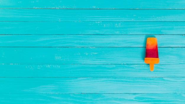 Heldere fruitijslolly op een houten oppervlakte Gratis Foto