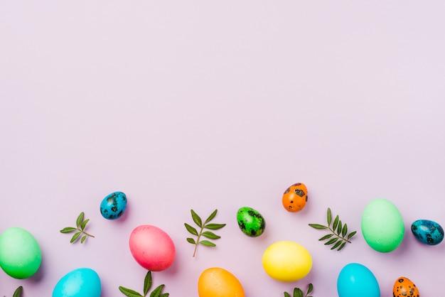 Heldere inzameling van rij van gekleurde eieren dichtbij bladeren Gratis Foto