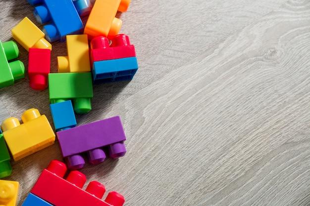 Heldere plastic bouwblokken op grijze houten achtergrond als achtergrond. speelgoed ontwikkelen. vroeg leren. bovenaanzicht. Premium Foto