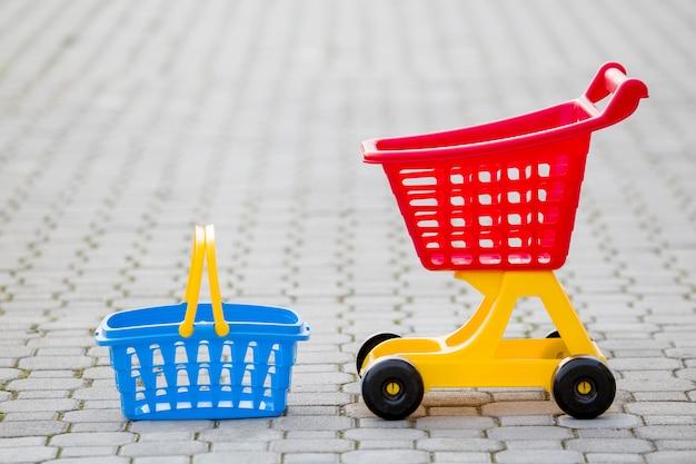 Heldere plastic kleurrijke speelgoed, winkelwagentje en mand buitenshuis Premium Foto