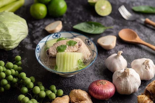 Heldere soep met kip met groen uitkomen met knoflook, citroen, ui, rode ui, champignons en basilicum Gratis Foto