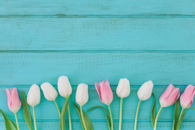 Heldere tulpenbloemen op houten lijst Gratis Foto