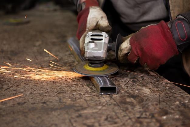 Heldere vonken vliegen wanneer de arbeider de metalen structuur maalt. Premium Foto
