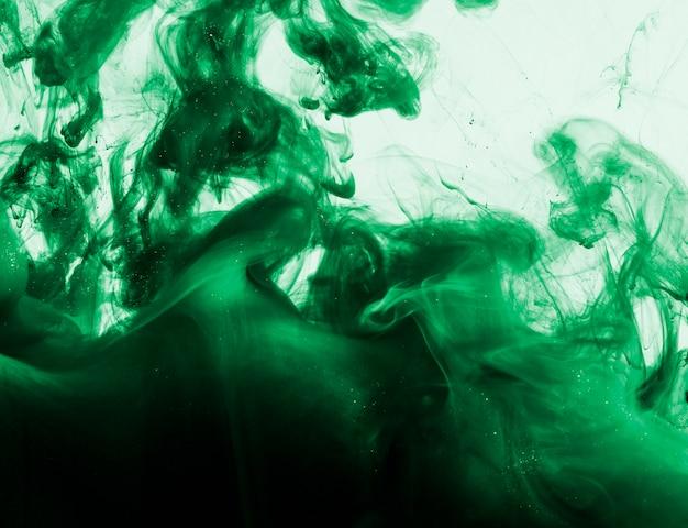 Heldergroene wolk van pigment in vloeistof Gratis Foto