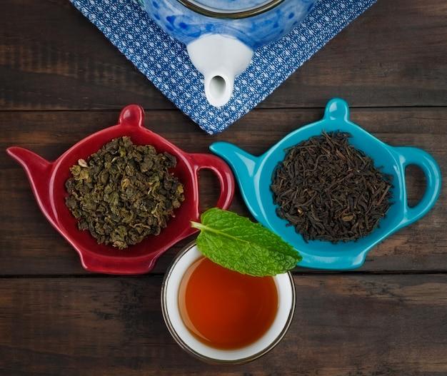 Hele blad thee met theepot en kopje met munt op houten tafel Premium Foto