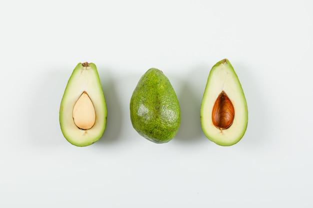 Hele en gesneden avocado op een witte ondergrond. bovenaanzicht. Gratis Foto