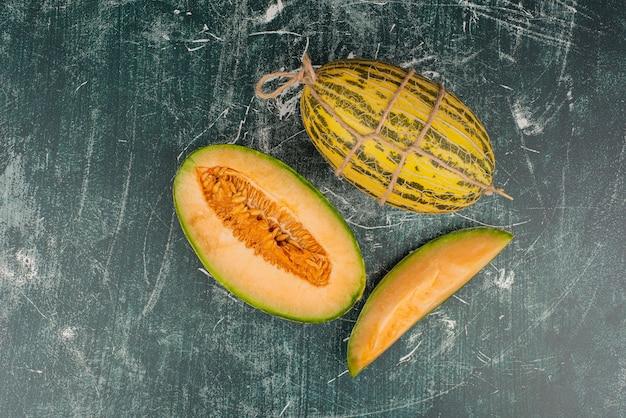Hele en gesneden meloenen op marmeren oppervlak. Gratis Foto