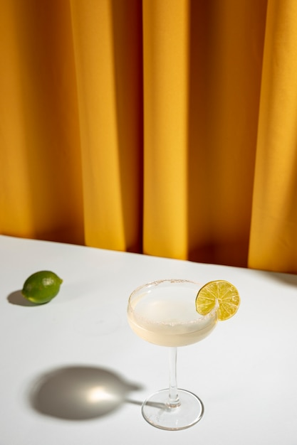 Hele limoen met margarita-cocktail in schotelglas op tafel bij het gordijn Gratis Foto