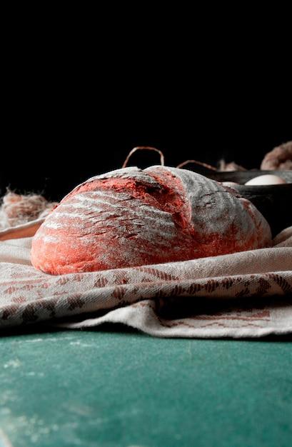 Hele ronde traditionele brood met bloem op de bovenkant op een bruine rustieke handdoek op een stenen tafel. Gratis Foto