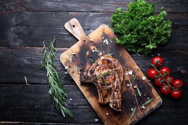 Hele stuk vlees op een snijplank, sappige en aromatische biefstuk, gegrild, groenten op tafel. plaats voor tekst. Premium Foto