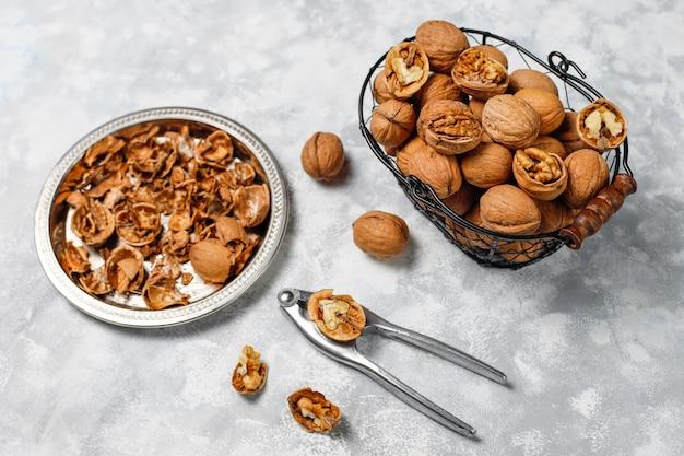 Hele walnoten in de schaal in voedsel metalen mand, walnoot kernels. bovenaanzicht op beton Gratis Foto