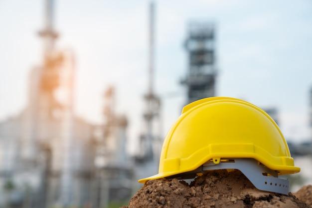 Helm van de ingenieur die van de raffinaderijindustrie ppe dragen bij raffinaderijbouwwerf Premium Foto