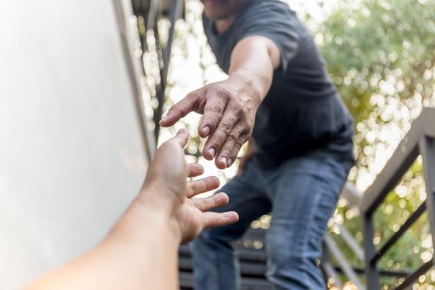 Help begrip handen reiken om elkaar te helpen met bokeh achtergrond. Premium Foto