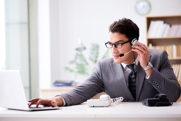 Helpdeskexploitant die op telefoon in bureau spreekt Premium Foto