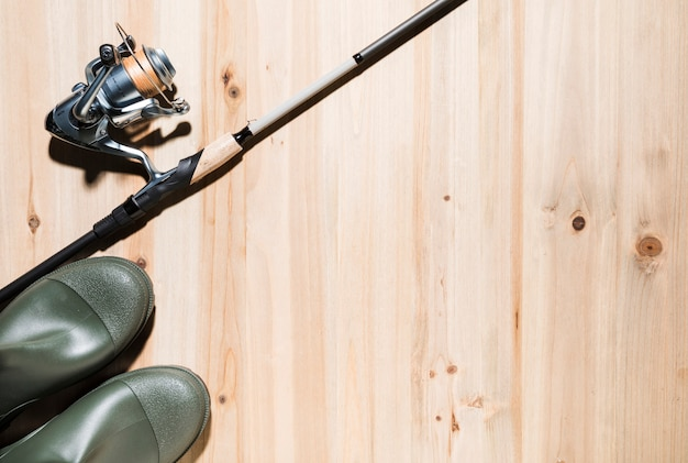 Hengel en visserijhaspel met rubberlaarzen op houten oppervlakte Gratis Foto