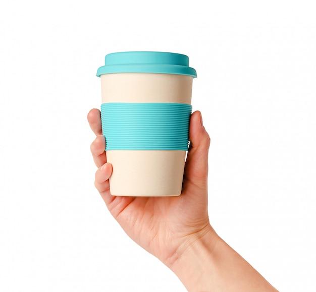 Herbruikbare bamboe koffiekop met siliconen houder in vrouwelijke hand. op wit wordt geïsoleerd. levensstijl zonder afval. Premium Foto