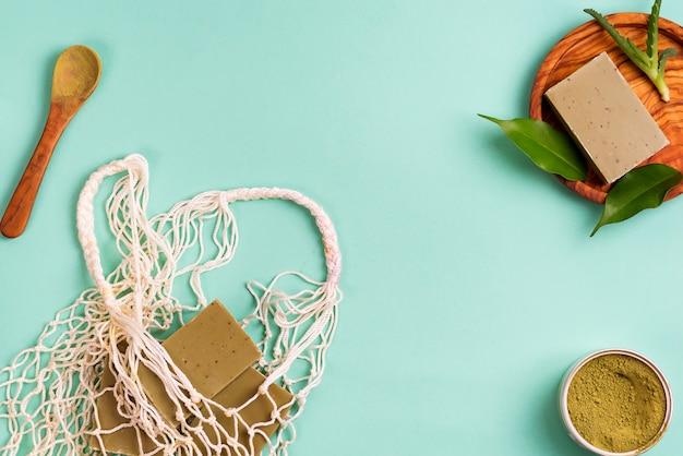 Herbruikbare boodschappentassen met handgemaakte olijfzeep, groene bladeren en groen poeder op blauw. geen afvalconcept. geen plastic. Premium Foto