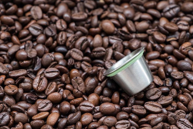 Herbruikbare metalen koffiecapsule op de donker gebrande koffieboon. Premium Foto