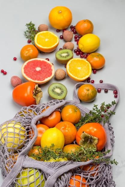 Herbruikbare netzak met fruit. mandarijnen, grapefruit, kiwi, druiven en snijbiet bladeren op tafel. Premium Foto