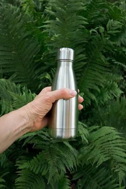 Herbruikbare roestvrijstalen thermosfles voor water in de vrouwelijke hand om de waterreserves van het lichaam aan te vullen tegen de achtergrond van varenbladeren. Premium Foto