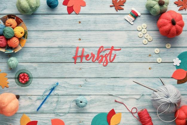 Herbst betekent herfst in het duits. tekst uit papier geknipt. wolbundels, garenballen, esdoornbladeren op verouderd lichtblauw hout. Premium Foto