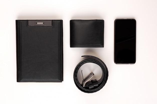 Heren set. totaal zwart. zwart lederen dagboek, zwart lederen riem, zwart lederen portemonnee en telefoon op een witte achtergrond. uitzicht van boven. Premium Foto