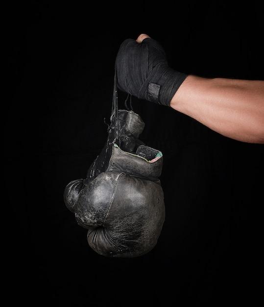 Herenarm gewikkeld in een zwart elastisch sportverband houdt een paar oude vintage lederen bokshandschoenen vast Premium Foto